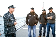"Willie and Jep Robertson of A&E's ""Duck Dynasty"" and Nationals first baseman Adam LaRoche listen to a sailor talk about his responsibilities aboard the USS Stout in Greeece on December 7. The trio is in the region as part of the 2013 Chairman USO Holiday Tour led by General Martin Dempsey. (Mike Clifton/USO)"